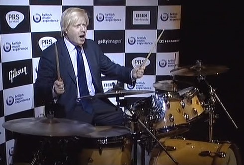 Boris at a drum kit, sticks aloft